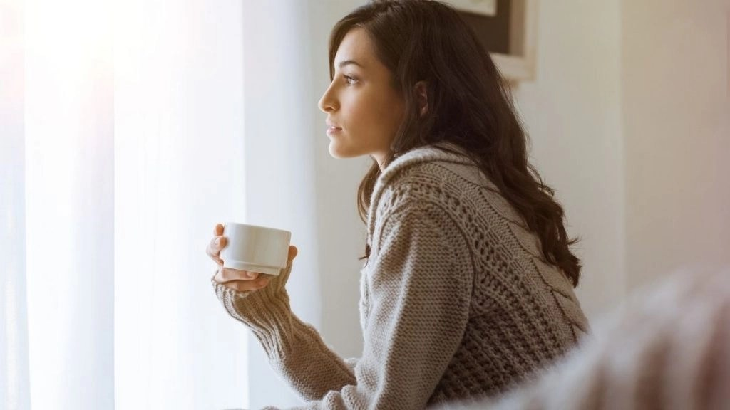 How to change your mindset woman looking out window drinking tea.