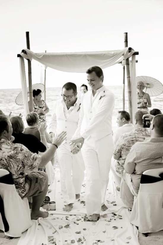 Casamento gay na praia: noivos de terno branco