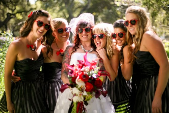 Noiva e madrinhas usando óculos escuros de coração vermelhos em casamento. Foto: Anna Joy.