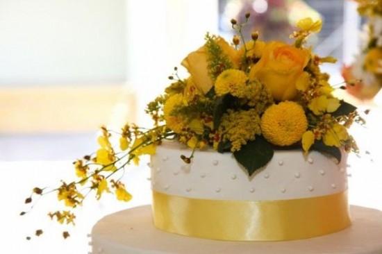 Bolo de casamento de bolinhas com fita amarela.