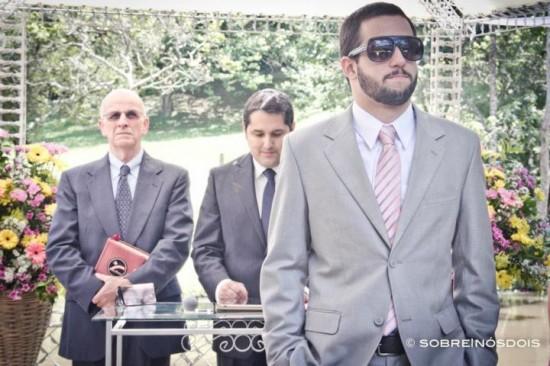 Noivo em casamento no campo com terno cinza e gravata rosa. Foto: Sobre Nós Dois.