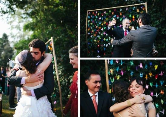 Casamento ao ar livre: noivos cumprimentando padrinhos em altar decorado com cortina de tsururs coloridos. Foto: Frankie e Marília.