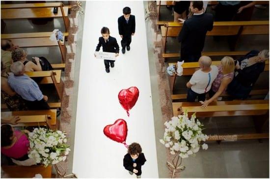 Casamento: pajem entra na cerimônia carregando balões de coração de gás. Foto: Beth Esquinatti.