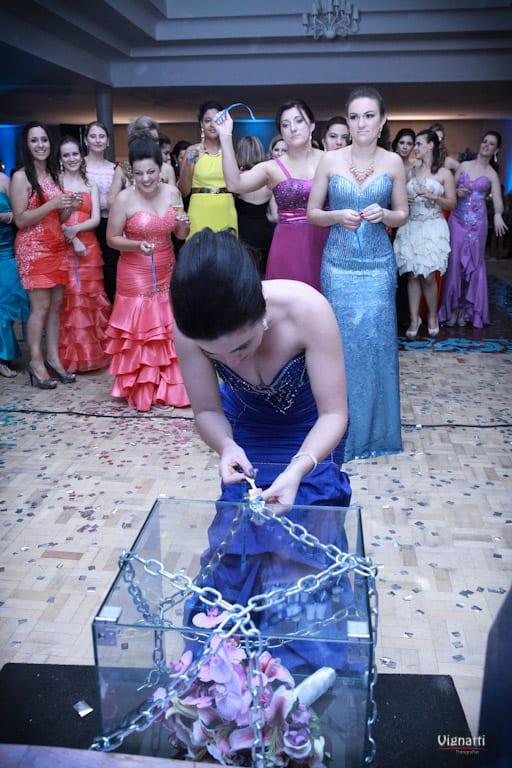 Convidada tenta abrir cofre com buquê de noiva em casamento. Foto: Vignatti Fotografias.