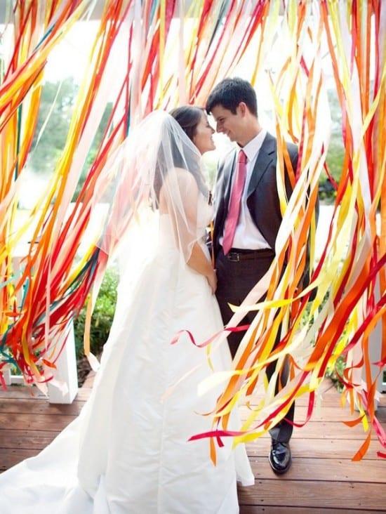 Casamento ao ar livre: altar branco com cortina de fitas coloridas em vermelho, amarelo, laranja e azul. Foto: Nancy Ray.