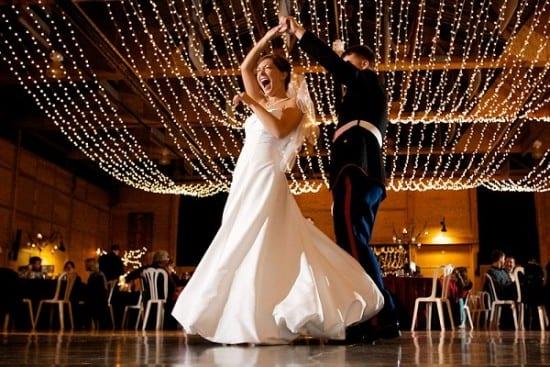 Decoração de casamento com luzinhas no teto do salão e casal dançando. Foto: Craig Mitchelldyer.