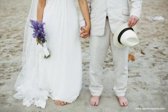 Noivos descalços na areia em casamento na praia. Danilo Siqueira.