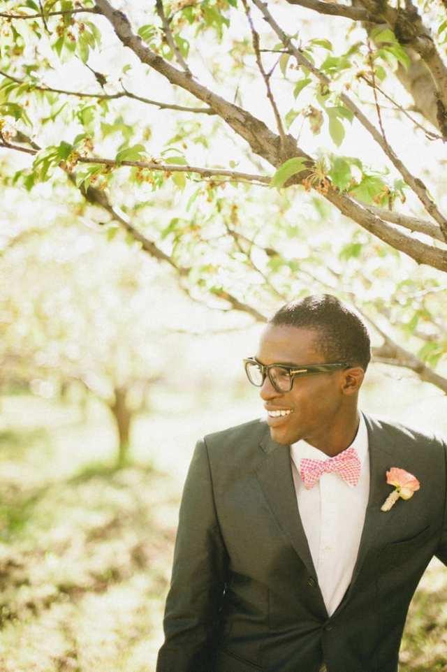 """Noivo negro com terno cinza escuro, gravata borboleta xadrez vermelha, flor na lapela e óculos de armação grossa """"nerd"""". Foto: David Newrirk."""