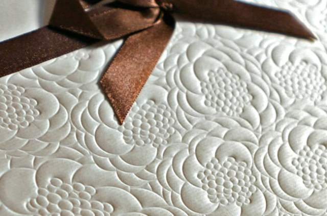 Detalhe do convite de casamento com envelope em relevo floral e fita marrom. Da Dom Bosco.