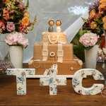Bolo de casamento em forma de mala de viagem com noivinhos de topo de bolo e letras de madeira na mesa com iniciais dos noivos. Foto: André Pinnola
