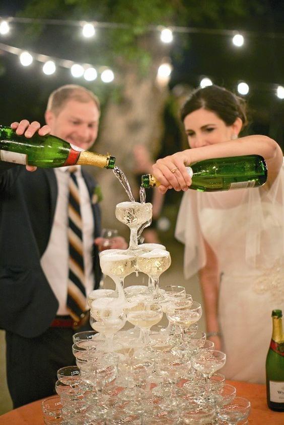 Torre de champanhe em cascata em casamento com noiva e noivo. Foto: Mel & Co.