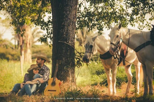 Ensaio de casamento pre-wedding estilo cowboy sertanejo, com os noivos Laurenice e Allison descansando do passeio a cavalo tocando violão. Foto: Herbeth Brand.