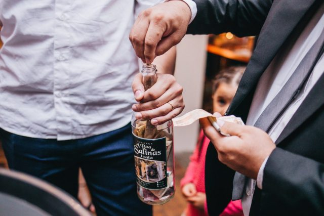 Casamento Dani e Raul: noivo passa a gravata com garrafa. Foto: Canvas Ateliê.