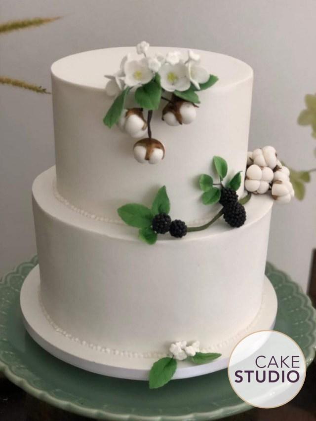 Bolo de casamento de 2 andares, branco com detalhes com folhagens, frutas vermelhas, flores e algodão. Feito por Cake Studio ( contato@cakestudio.com.br | Whatsapp: (11) 96882-2623 ).