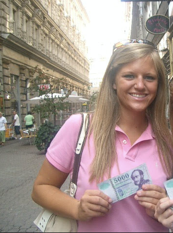 Girl traveling abroad, holding up foreign currency. Girl still has leftover foreign currency ten years later.