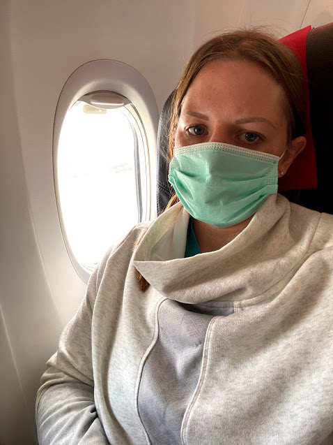 person wearing a mask on an airplane while traveling in a pandemic