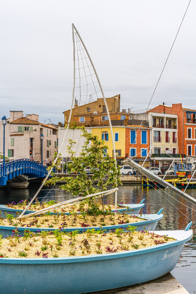 flowers in the shape of a boat and colorful buildings in the city of Martigues, France