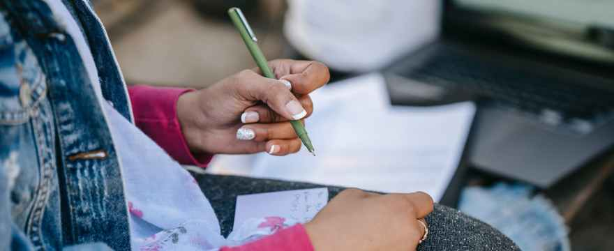 crop female student writing notes while sitting with laptop on bench