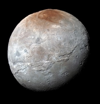 Pluto's largest moon Charon has an unusual reddish-colored north polar cap, and scientists think it results from methane escaping Pluto's atmosphere and condensing on Charon's cold surface. Sunlight then converts the methane ice into reddish tholins. Photo Credit: NASA/JHUAPL/SwRI