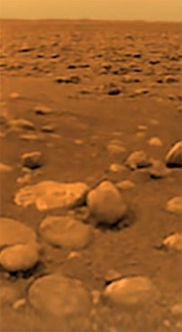 """The surface of Titan as seen, for the first time ever, by the Huygens probe on Jan. 14, 2005. The """"rocks"""" are actually rounded blocks of solid water ice. Photo Credit: ESA/NASA/JPL/University of Arizona"""