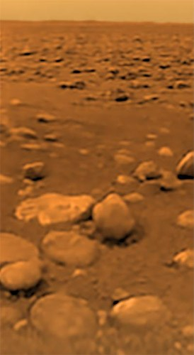 "The surface of Titan as seen, for the first time ever, by the Huygens probe on Jan. 14, 2005. The ""rocks"" are actually rounded blocks of solid water ice. Photo Credit: ESA/NASA/JPL/University of Arizona"