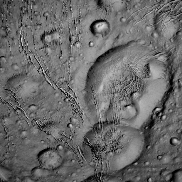 Raw image from the Oct. 14 flyby, showing craters and cracks in the icy surface, as well as other interesting textures. Image Credit: NASA/JPL-Caltech/Space Science Institute