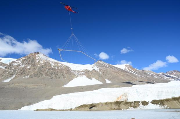The SkyTEM sensor suspended beneath a helicopter over Blood Falls and the Taylor Glacier in Antarctica. Photo Credit: L. Jansan