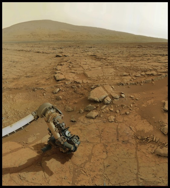 View of Curiosity's robotic arm with drill in place and Mount Sharp in the background. Click for larger version. Credit: NASA / JPL-Caltech / Olivier de Goursac