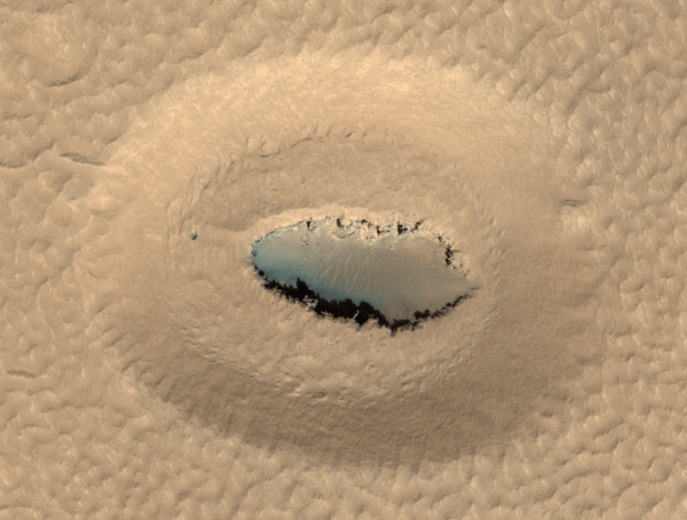 Oval pit or crater with opening in the bottom, as photographed near Galaxias Chaos on Mars by the HiRISE camera on the Mars Reconnaissance Orbiter spacecraft. Click for larger version. Credit: NASA/JPL/University of Arizona