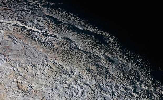 "Extended colour image showing the ""snakeskin"" terrain in the Tartarus Dorsa region, a mixture of blue-grey ridges and other reddish material. Image Credit: NASA/JHUAPL/SWRI"