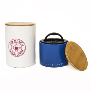 Photo of a blue canister with lid and a larger white canister with the words New Mexico Pinon Coffee written in red.