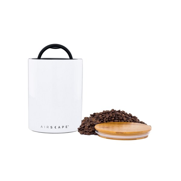 Photo of a white airscape ceramic coffee storage container with wooden lid and whole coffee beans.