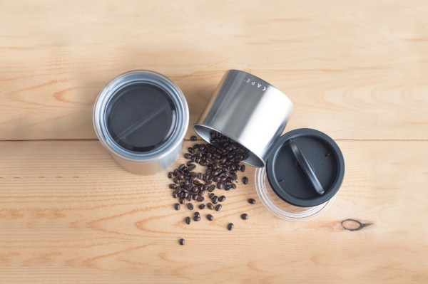 Photo of Airscape stainless steel canisters. One has seal and lid on. Other is on its side with coffee beans; lids are to the right.