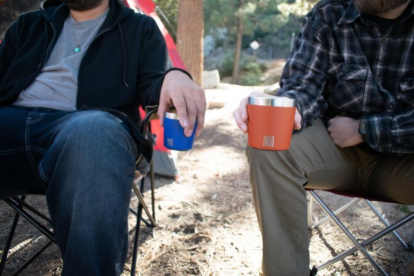 Photo of two people sitting in camp chairs in the woods, holding BruTrek Camp Cups
