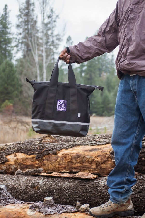 Photo of man standing in a forest, holding the black BruTrek logo Camp Coffee Kit Bag