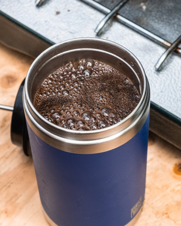 Photo of blue BruTrek coffee french press with the lid off and it filled with coffee and water all sitting against a camping stove.