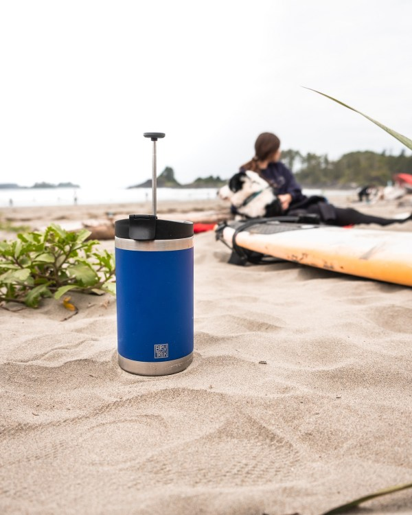 Photo of a blue coffee press sitting on the beach sand while a surfer and his dog are sitting in the background.