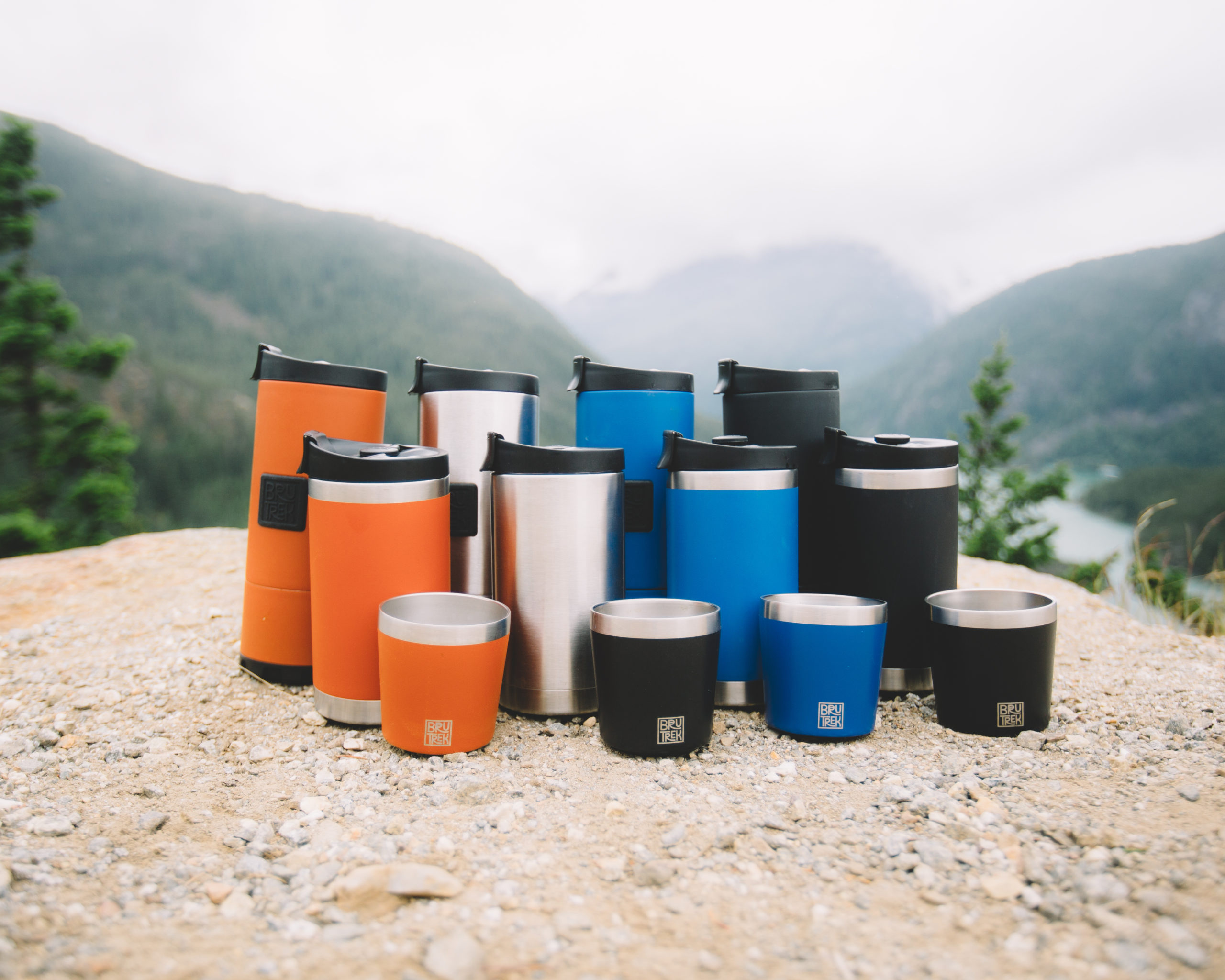 photo of brutrek french presses and cups arranged by color on a rock with mountains in the background