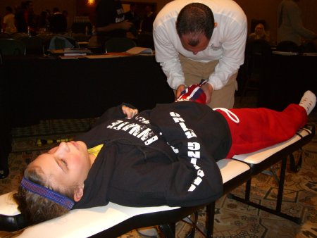 chiropractor assessing individual on adjusting table