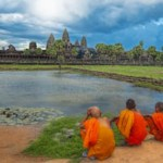 Monks watching the sunset over Angkor Wat from the lake