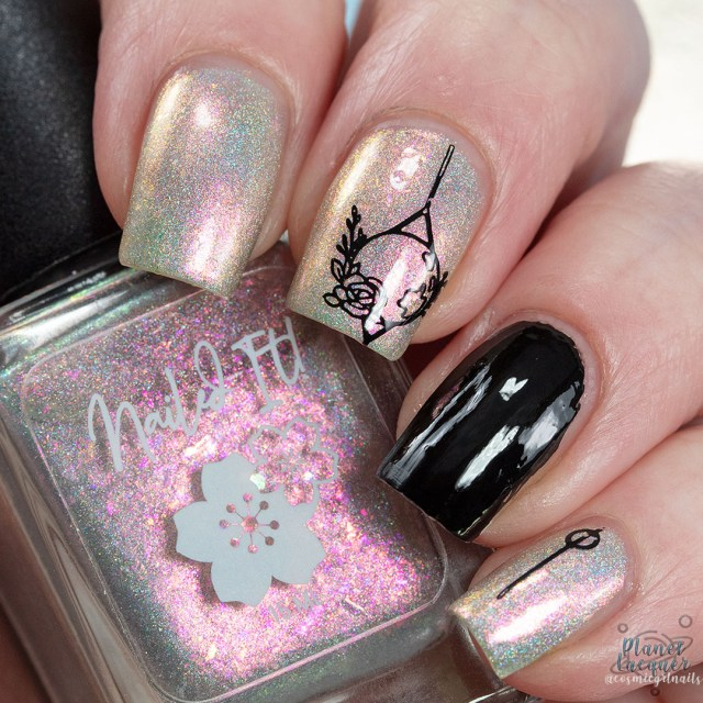 Pictured is a swatch of four fingers painted with nail art on middle finger by Britta in the nail polish Metamorphosis apart of the four piece Secret Garden Collection by Nailed It! Nail Polish.