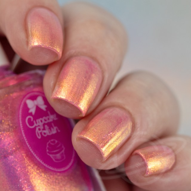 Pictured here is a four finger nail swatch of Cupcake Nail Polish Pink Sand a light pink nail polish packed with red to green to gold iridescent aurora shimmers photographed in artificial daylight bulbs