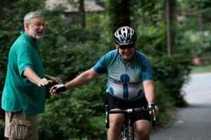 Norm Torkelson of Stockton high fives Michael Schulz of Hamilton on the last leg of the journey as Schulz climbs a hill. Photo: Jeanne Imbrigiotta.