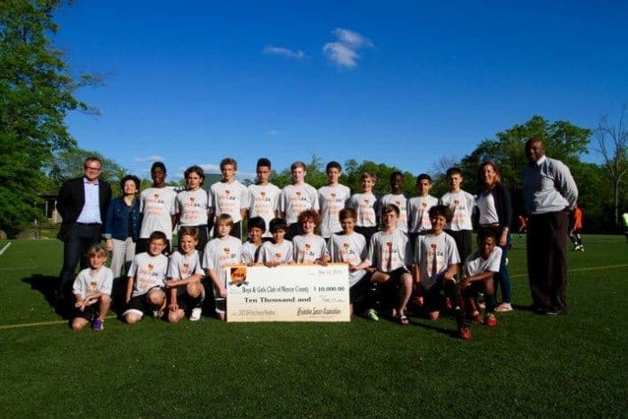 Princeton Soccer Association members present a check for $10,000 to the Boys and Girls Club.
