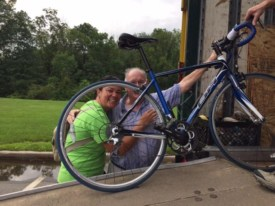 Bill Hogan, 90, president emeritus of the Anchor House Foundation, get a hug from cyclist Kilani DiGiacomo of Lawrence as he helps her load her bike Thursday night.