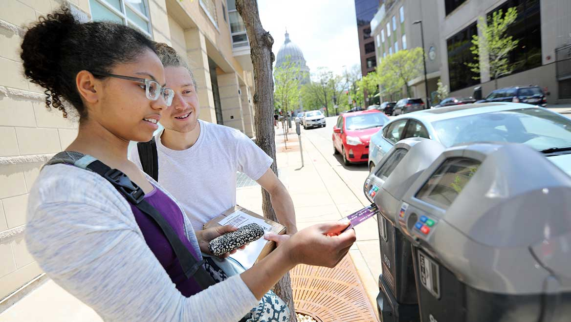 """The coordinated parking rates in Madison, WI, create higher on-street parking rates for short-term access to the curb. Lauralyn Rosenberger, left, and Mason Purtell, use a """"smart"""" meter to pay for their downtown parking space. Photo by Amber Arnold/State Journal."""