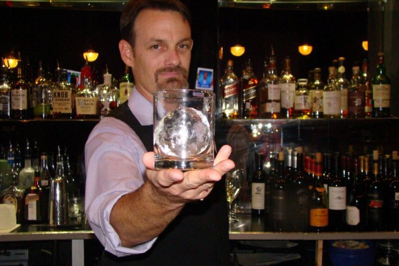 Chris Norton bartending holds up ice sculpted specialty cocktail in Frisco Edoko Sushi