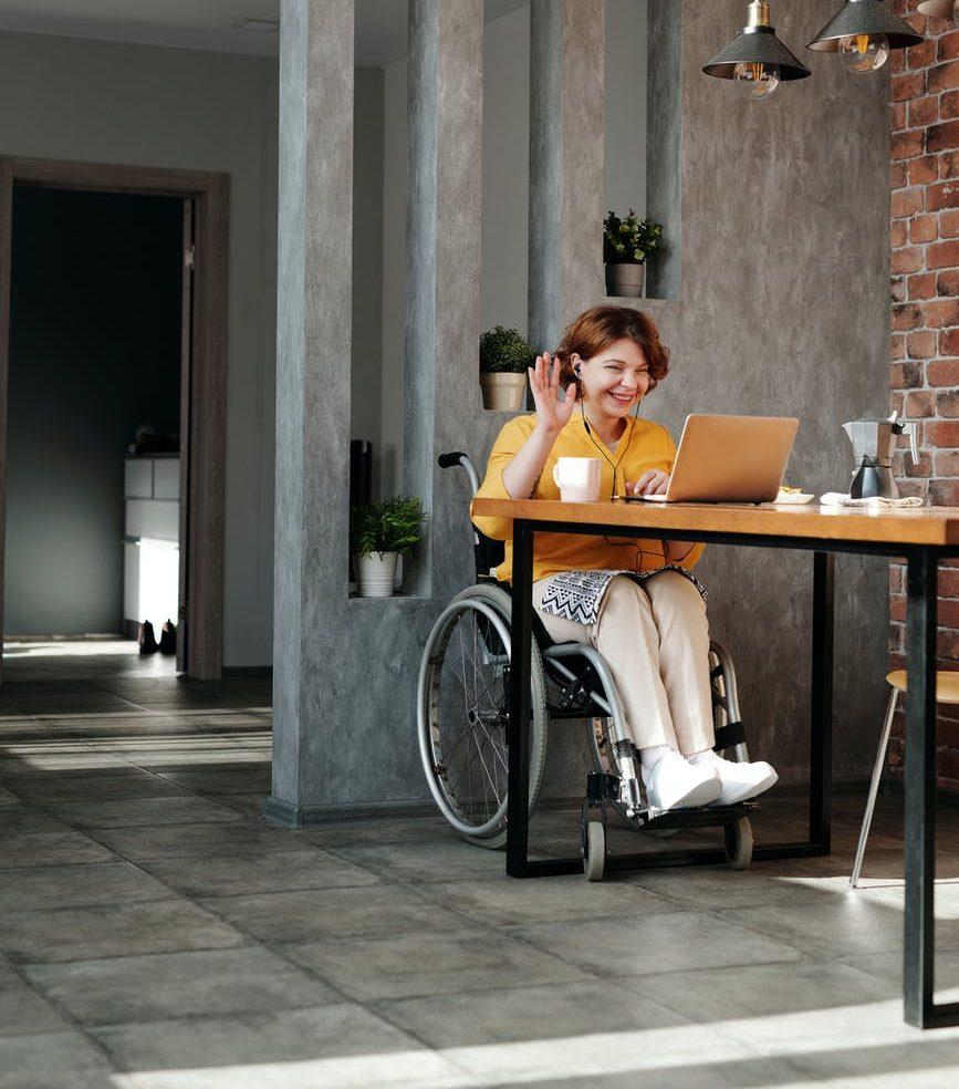 woman in orange tank top sitting on black wheelchair