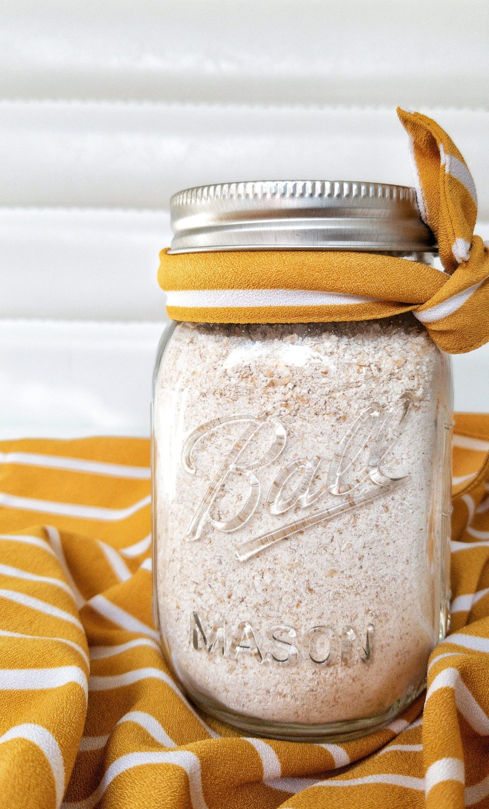Oat flour in a glass mason jar tied with a yellow and white ribbon
