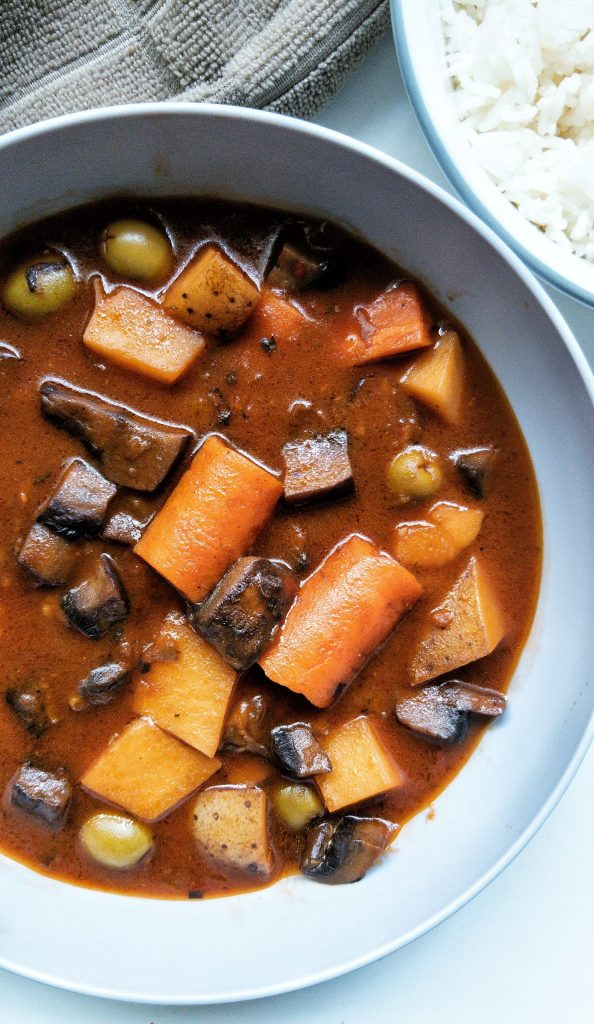 """Puerto Rican vegan beef stew or """"carne guisda"""" in a grey bowl with a side of white rice"""